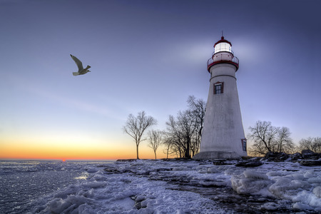 erie: The historic Marblehead Lighthouse in Northwest Ohio sits along the rocky shores of the frozen Lake Erie. Seen here in winter with a colorful sunrise and snow on the ground as a seagull flys by. Stock Photo