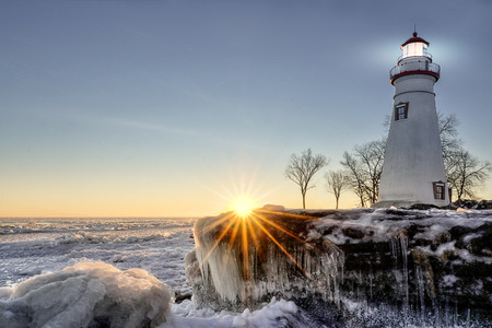 The historic Marblehead Lighthouse in Northwest Ohio sits along the rocky shores of the frozen Lake Erie. Seen here in winter with a colorful sunrise and snow and ice. Stock Photo