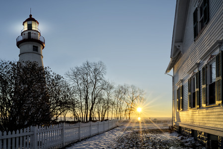 erie: The historic Marblehead Lighthouse in Northwest Ohio sits along the rocky shores of the frozen Lake Erie. Seen here in winter with a beautiful sunrise and snow on the ground.