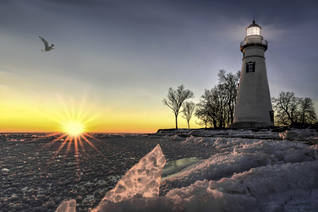 winter sunrise: The historic Marblehead Lighthouse in Northwest Ohio sits along the rocky shores of Lake Erie in winter at sunrise.