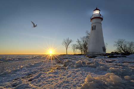 erie: The historic Marblehead Lighthouse in Northwest Ohio sits along the rocky shores of the frozen Lake Erie in winter with a colorful sunrise and snow on the ground.
