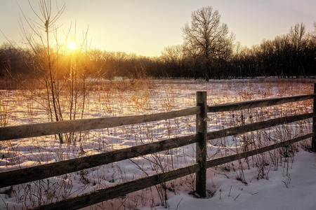 split road: A snowy winter sunrise scene along a rural country road. Includes fresh snow and a split rail fence. Stock Photo