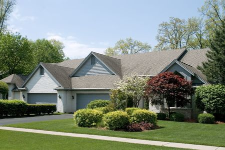 Beautiful white brick ranch home featuring beautiful landscaping.