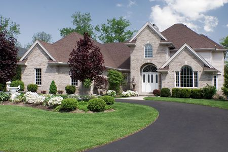 Beautiful and large brown brick home featuring a complex roof design and formal fantastic landscaping.