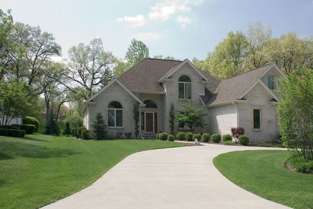 realty residence: Beautiful beige brick home featuring a complex roof design, circular driveway and formal landscaping. Stock Photo
