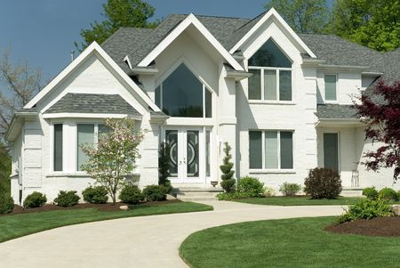 Beautiful white brick home featuring a modern architectural design with large windows and a circular driveway. The yard is completed with formal landscaping. Stock Photo