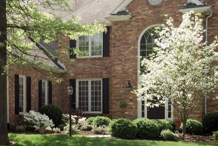 realty residence: Beautiful red brick home featuring  formal landscaping.