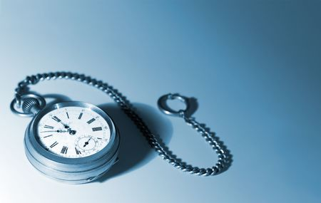 Old silver pocket watch with a chain; focus on dial, blue tinted; on a white background