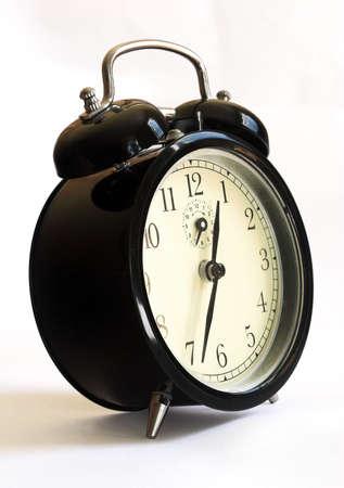 Black retro-styled alarm clock - close up on white background.