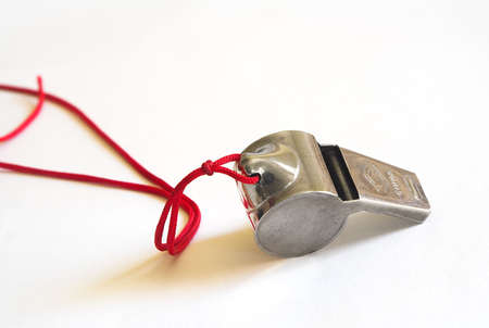 squeal: Fischietto di metallo su un tiro cavo rosso su sfondo bianco Archivio Fotografico