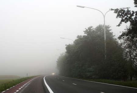 Misty main road with car headlights visible through the mist photo