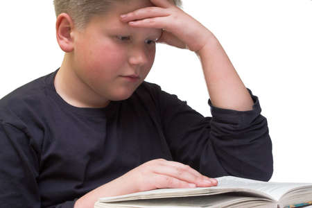 Young teenager boy reading a book close up on white background