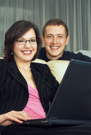 Business couple of smiling young adults; sitting with a laptop