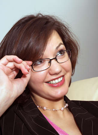 Young attractive lady looking up and touching her glasses; business dress; photo