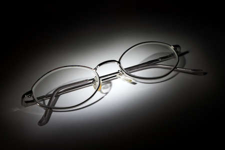 myopic: Closed glasses on white background in the darkness Stock Photo