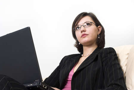 young business woman working with laptop on her laps; sitting on a sofa in a lounge; wearing glasses