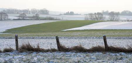Fields covered by snow behind a rugged fence Stock Photo - 725392