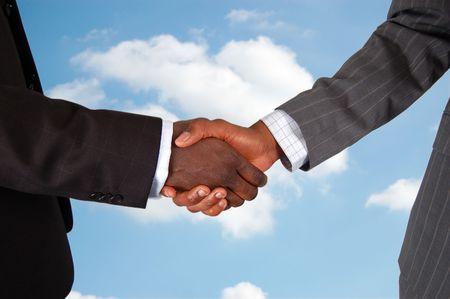 """unificar: Esta es una imagen de dos cuerpos masculinos, en representaci�n de los empresarios en un apret�n de manos de acuerdo. Nubes de antecedentes para representar a tratar de """"Cielo""""."""