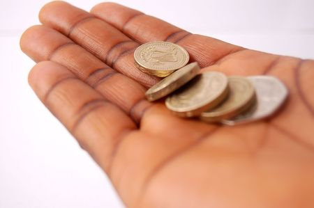 This is an image of a hand with pound coins on it.