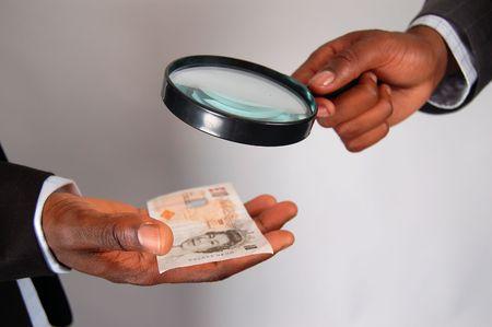 vals geld: Dit is een afbeelding van de handen van twee mannen de controle op de rechtmatigheid van een tien pond nota (uk geld).