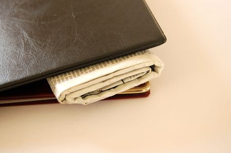 This is an image of a pair of portfolios with a newspaper in between them. photo