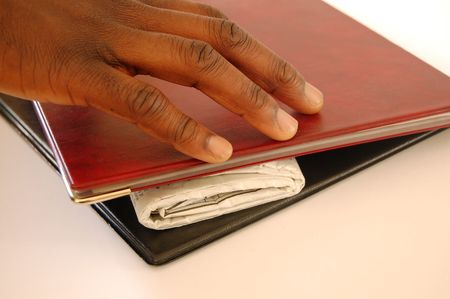 This is an image of a hand reaching for a newspaper, underneath a portfolio. photo