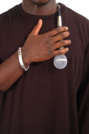 This is an image of man with his hand against a microphone to his chest. Stock Photo