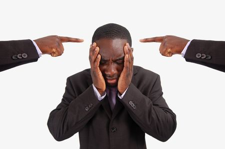 This is an image of a man feeling guilty, with two fingers pointing at him. He is at the centre of blame. Stock Photo