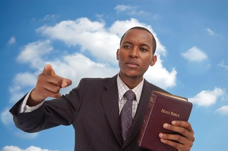 preach: This is an image of man holding a bible against a cloudsky background. This image can be used to represent Heavenly Message,sermon, preaching etc... Stock Photo