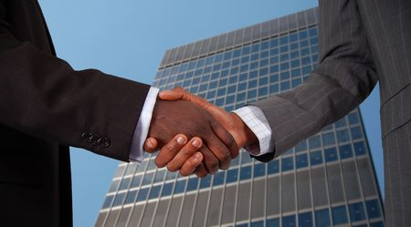 This is an image of two business hands performing a handshake, with a corporate building in the background.
