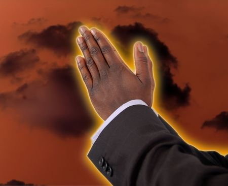 This is an image of businessman with hands in a prayer posture. This is image can be used to represent Prayer Of Fire themes. The yelloworange glow round the fingers represent fire.  photo