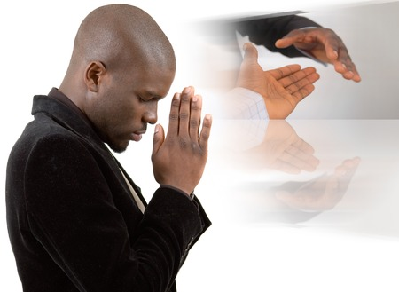 This is an image of a businessman praying for success. This image can be used to represent Praying for Peace or Praying for a Deal etc..