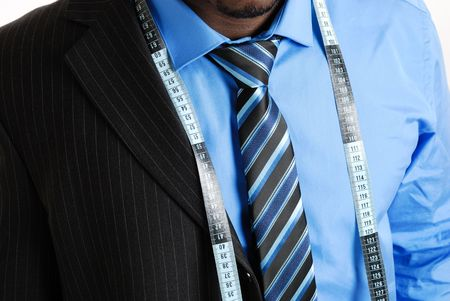 This is an image of business man wearing a tape measure across his suit and shirt. Fashion concept.