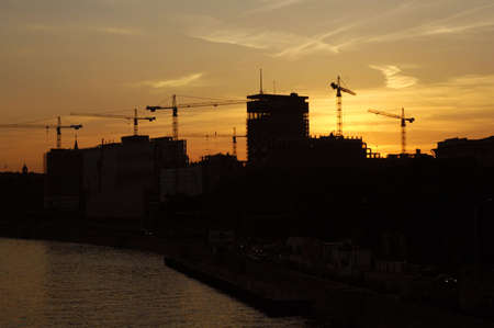 construction of a building, cranes and other machinery as silhouettes against a background of red sunset sky Stock Photo