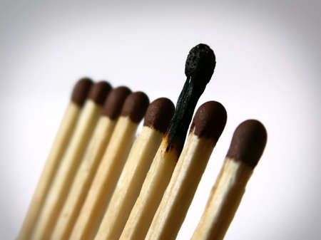 Close-up photo of several matches in a row with one burnt Stock Photo