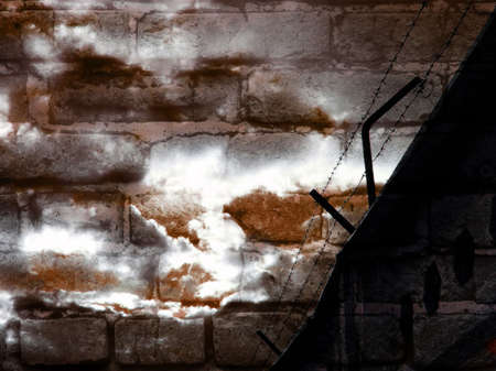 a barbed wire against background of a brick wall and cloudy sky