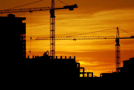 an erection: construction of a building, cranes and other machinery as silhouettes against a background of red sunset sky Stock Photo