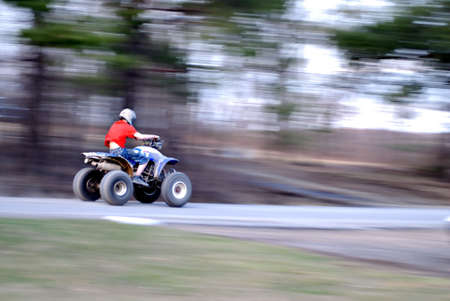 A youngster breaks the law as he rides the roadway on his four wheeler. Atleast he has his helmet on. Stock Photo