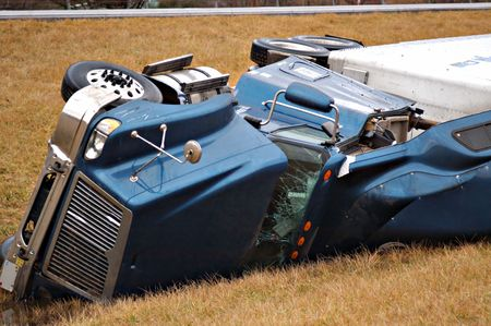 wreckage: A tractor trailer on its side in the median after a roll over accident.