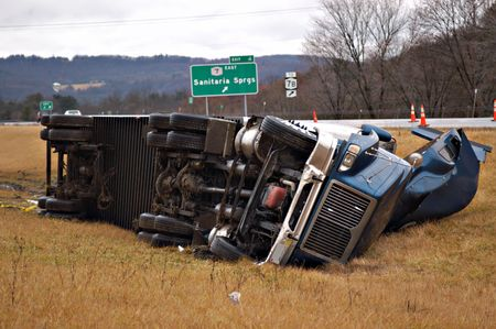 wheel truck: A tractor trailer on its side in the median after a roll over accident.