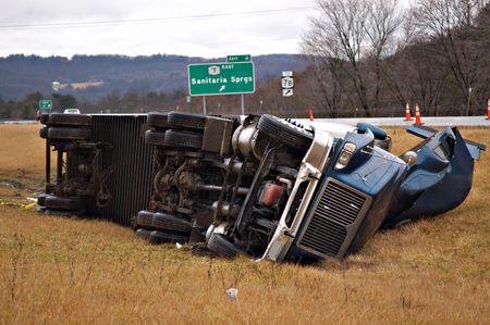 mediaan: Een trekker-trailer op zijn kant in de mediaan na een roll over ongeluk.