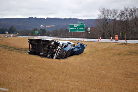 semi trailer: A tractor trailer on its side in the median after a roll over accident.