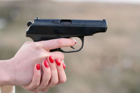 womans: womans hand holding a gun Stock Photo