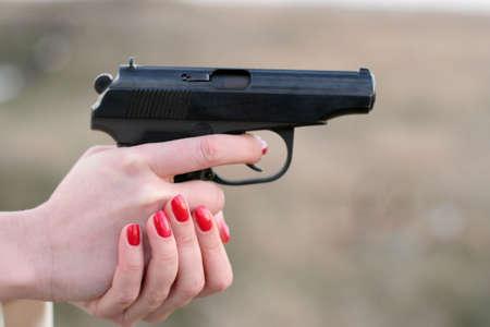 killer: womans hand holding a gun Stock Photo