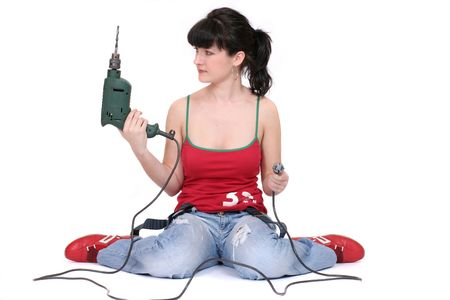 drill floor: woman sitting with a drill on the floor. isolated