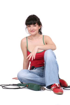 drill floor: smiling woman with a drill sitting on the floor. Isolated Stock Photo