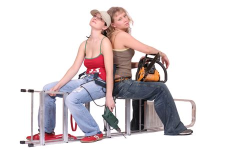 Two tired women sit near each other on stepladder on white background photo