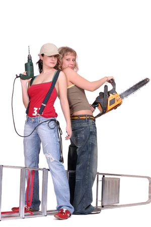 Two women stand near each other on white background holding a chainsaw and a drill