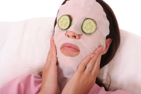 young woman with a cosmetic mask and cucumber