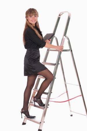 a smiling business woman with a laptop climbing ladder